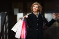 Happy young woman shopping with bags against a mall entrance Royalty Free Stock Photography