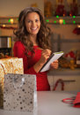 Happy young woman with shopping bags checking list of gifts in christmas decorated kitchen Stock Image