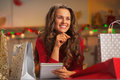 Happy young woman with shopping bags in kitchen christmas decorated checking list of gifts Royalty Free Stock Photo