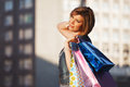 Happy young woman with shopping bags walking on the city street Royalty Free Stock Photography