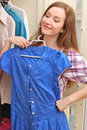 Happy young woman shopping for clothes at the mall selecting a dress Royalty Free Stock Photos