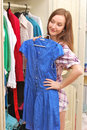 Happy young woman shopping for clothes at the mall selecting a dress Stock Photography