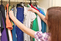 Happy young woman shopping for clothes at the mall selecting a dress Royalty Free Stock Photo