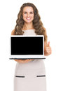 Happy young woman showing laptop blank screen showing thumbs up Royalty Free Stock Photo