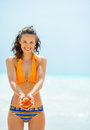 Happy young woman showing shell on beach portrait of Royalty Free Stock Photography