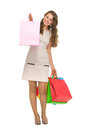 Happy young woman showing shopping bags Royalty Free Stock Photography