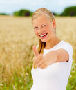 Happy young woman showing thumbs up at a field Stock Photo