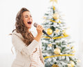 Happy young woman singing near christmas tree in living room Stock Images
