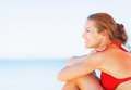 Happy young woman sitting on beach and looking on copy space in bikini Royalty Free Stock Photos