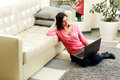 Happy young woman sitting on the floor with laptop at home Stock Photography