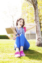 Happy young woman sitting on grass  listening to music and singing. Royalty Free Stock Photo