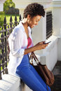 Happy young woman sitting outdoors and using mobile phone Royalty Free Stock Photo