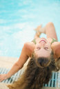 Happy young woman sitting at poolside with long hair Stock Photos