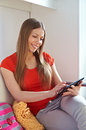 Happy young woman sitting sofa using tablet pc Royalty Free Stock Photos