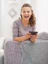 Happy young woman sitting on sofa and writing sms in living room Royalty Free Stock Photo