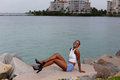 Happy young woman sitting by the water stock photo of a beautiful female model in miami beach Royalty Free Stock Photography