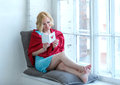 Happy young woman sitting on windowsill with love postcard Royalty Free Stock Photo