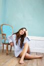 Happy young woman sitting on wood floor and relaxing at home portrait of a Royalty Free Stock Photography