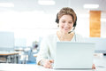 Happy young woman sitting and working with laptop using headset charming in office Royalty Free Stock Photography