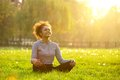 Happy young woman sitting in yoga position Royalty Free Stock Photo