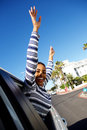Happy young woman smiling with arms raised outside car window Royalty Free Stock Photo