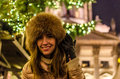 Happy young woman smiling at christmas market beautiful in fur cap and leather gloves staying on background of tree and near the Royalty Free Stock Photos