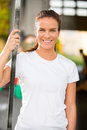 Happy young woman smiling at fitness gym center fit attractive and rests after workout a people workout in the background Royalty Free Stock Photos