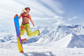 Happy young woman with snowboard jumping in winter sportswear Royalty Free Stock Photo