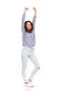 Happy young woman standing with arms raised smiling in sweater and torn jeans and looking away full length studio shot isolated on Stock Images
