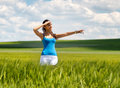 Happy young woman standing in a field pointing beautiful of green wheat shielding her eyes from the sun and to the right of Stock Image