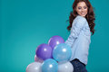 Happy young woman standing over blue wall and holding balloons.