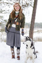 Happy young woman standing with siberian husky dog in winter forest Royalty Free Stock Photography