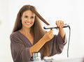 Happy young woman straightening hair with straightener in bathroom Royalty Free Stock Photography