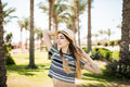 Happy young woman in summer clothes and sun hat at beach resort Royalty Free Stock Photo