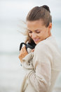 Happy young woman in sweater on beach with cup of hot beverage long hair Royalty Free Stock Photos