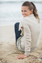 Happy young woman in sweater sitting on lonely beach with long hair Royalty Free Stock Image
