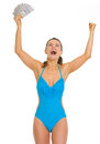 Happy young woman swimsuit fan dollars rejoicing success Stock Photo