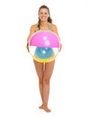 Happy young woman in swimsuit giving beach ball Royalty Free Stock Photo