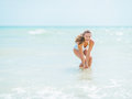 Happy young woman in swimsuit having fun time on sea shore pretty white Royalty Free Stock Photo