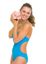Happy young woman swimsuit showing piggy bank isolated white Royalty Free Stock Images