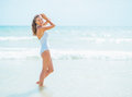 Happy young woman in swimsuit standing at seaside white Stock Photography