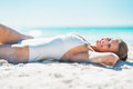 Happy young woman in swimsuit sunbathing on sandy beach white Stock Images