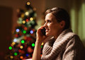 Happy young woman talking cell phone in front of christmas tree high resolution photo Stock Photos