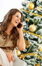 Happy young woman talking cell phone while sitting n