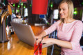 Happy young woman using laptop at bar counter Stock Photo