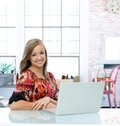 Happy young woman using laptop at home sitting desk Stock Photos