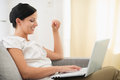 Happy young woman using laptop in living room Royalty Free Stock Photo