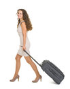 Happy young woman walking with wheels suitcase Royalty Free Stock Images