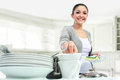 Happy young woman washing dishes in the kitchen Stock Photo