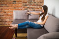Happy young woman watching tv on sofa at home Royalty Free Stock Photo